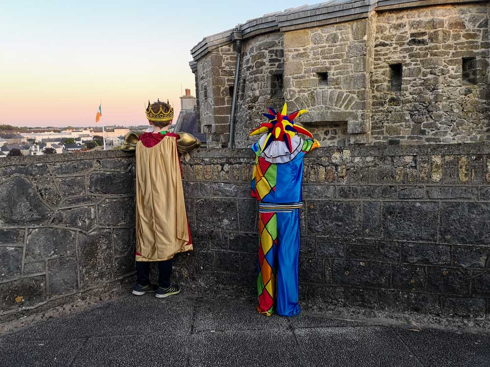 A young boy dressed as a King and his friend dressed as a Jester look down on to Athlone Castle's courtyard.