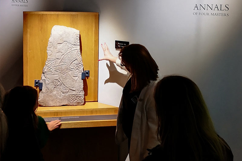 Athlone Castle tour guide presenting one of the stone slabs from early Christian times on display in the Early Settlement exhibition at Athlone Castle Visitor Centre.