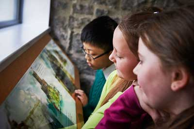 Three children taking in the illustrations of Athlone Castle development through Medieval times right up to the Anglo Norman era in our First 400 Years exhibition at Athlone Castle Visitor Centre.