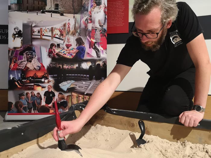 Athlone Castle team member David giving a demonstration on how an archaeological dig is executed. Here he is using a sand box full of sand and some tools such as a paintbrush to dig into the sand and see what he can discover.