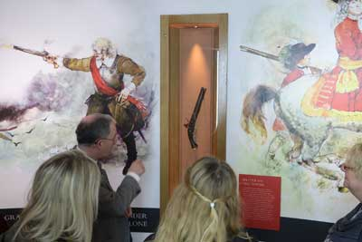A group of visitors listening to a presentation on the flintlock pistol which is on display in our Athlone Besieged exhibition at Athlone Castle Visitor Centre.