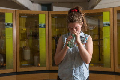 A visitor takes a closer look at a unique glass bottle in the museum's collection